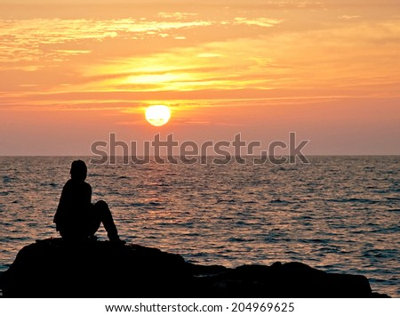 Silhouette of an unidentified person sitting by the rock facing the beach with the sun setting as background.