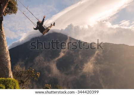 Silhouette Of An Young Happy Woman On A Swing, Swinging Over The Andes Mountains, Tungurahua Volcano In The Background, Tree House, Ecuador  - stock photo