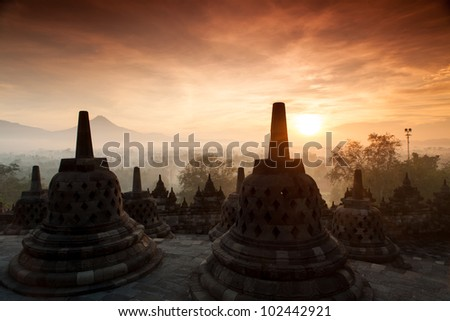 Silhouette of Ancient stupa Borobudur Temple, with sunrise in Yogyakarta, Java, Indonesia. - stock photo