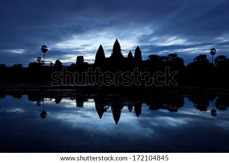 Silhouette of Angkor Wat complex at sunrise against dark blue sky.