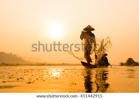 Silhouette of asia Fisherman net casting on the boat  on morning time sunrise - stock photo