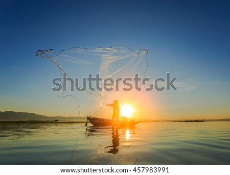 Silhouette of asian fisherman on wooden boat ,fisherman in action throwing a net for catching freshwater fish in nature river, traditional fishermen at the sunset near Galle in Sri Lanka. - stock photo