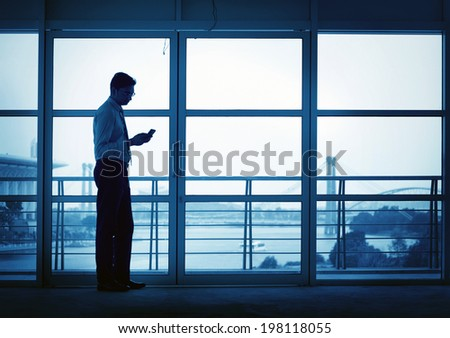 Silhouette of Asian Indian man using mobile phone in modern office building, blue tone. - stock photo