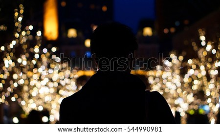 Silhouette of Asian man back, alone in Christmas illumination light in winter park