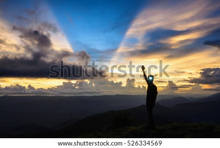 Silhouette of asian man on top mountain  hold camera and flashlight on head in evening sunset with golden cloud and sky in background