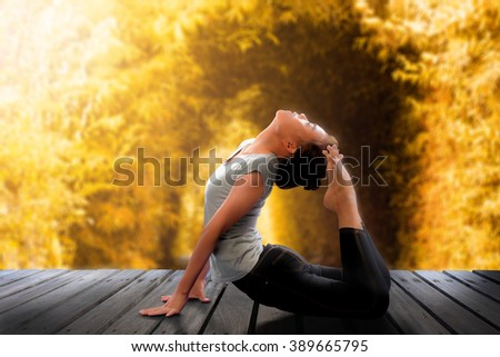 Silhouette of Asian woman yoga pose on the wooden bridge over blurry waterfall in the autumn forest at the sunrise in the morning. Images create dreaming light and surrealist style. - stock photo
