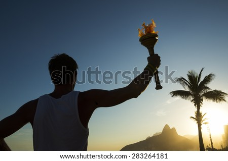 Silhouette of athlete standing with sport torch at the Rio de Janeiro Brazil sunset skyline at Ipanema Beach - stock photo