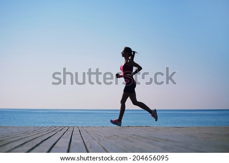 Silhouette of athletic female jogger with beautiful figure running on the pier, morning run on the beach, fitness and healthy lifestyle concept