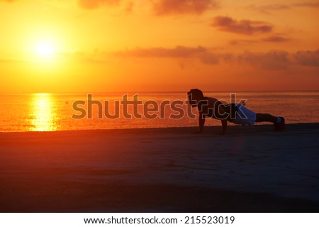 Silhouette of athletic runner warming up and doing some push ups on the beach, push ups or press ups exercise by young male runner man, fitness and healthy lifestyle concept - stock photo