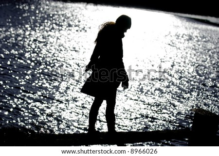 Silhouette of attractive woman at lake against sunlight reflections - stock photo