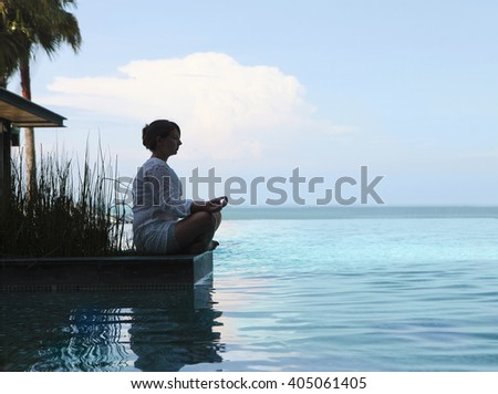 Silhouette of attractive woman sitting in meditating position by the pool - stock photo