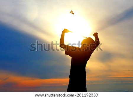 Silhouette of Badminton Player on the Sunset Sky Background