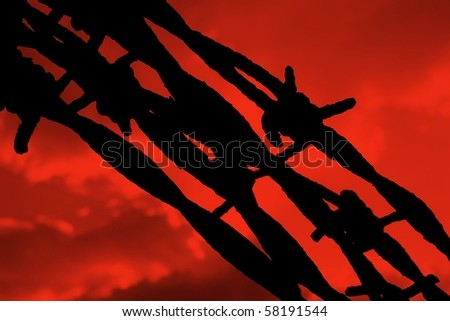 Silhouette of Barbed Wire against a Blood Red Sky - stock photo
