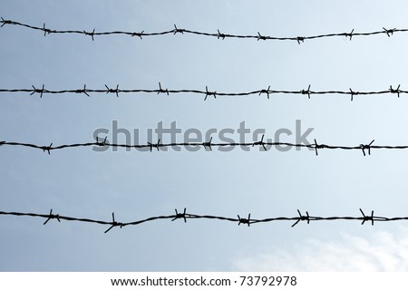 Silhouette of barbed wire on blue sky - stock photo