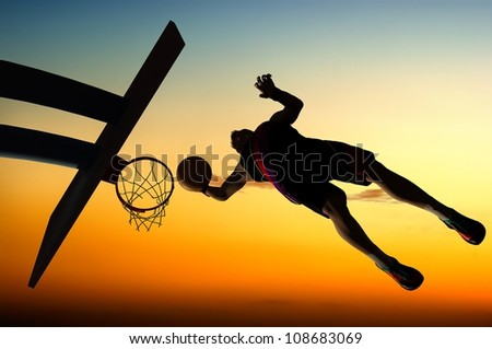 Silhouette of basketball against the sky. - stock photo