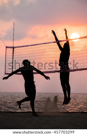 silhouette of beach Volleyball player on the beach and playground sand in sunset - stock photo