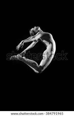 Silhouette of beautiful female in dancing jumping or flying on dark background. Black and white photography  - stock photo
