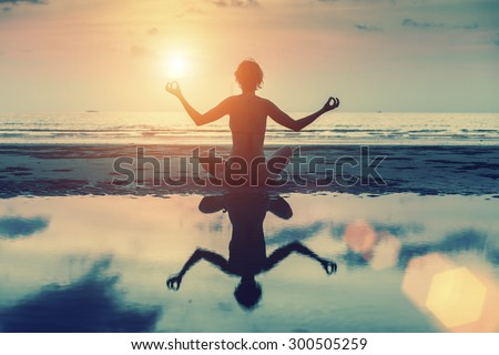 Silhouette of beautiful girl sitting on the beach during sunset and meditating in yoga pose.