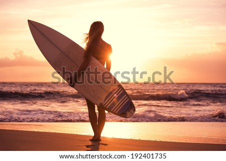Silhouette of beautiful surfer girl on the beach at sunset - stock photo