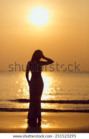 silhouette of beautiful young woman against beautiful sunset - stock photo