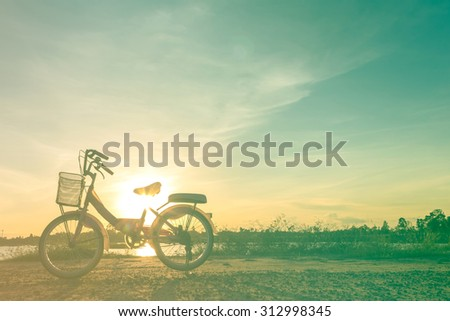 Silhouette of bicycle with background of sunset