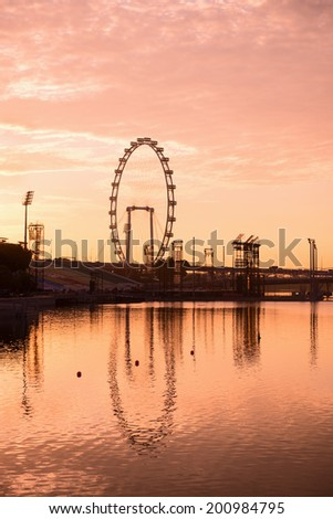 Silhouette of big ferris wheel in the pink sky with reflection in water - stock photo