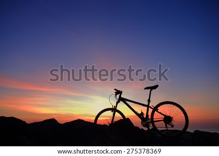 Silhouette of bike on rock mountain with sunrise twilight background. - stock photo