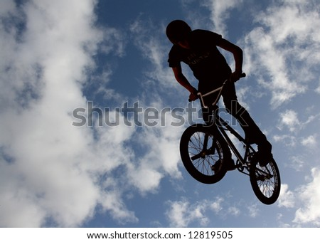 Silhouette of biker boy flying through the air
