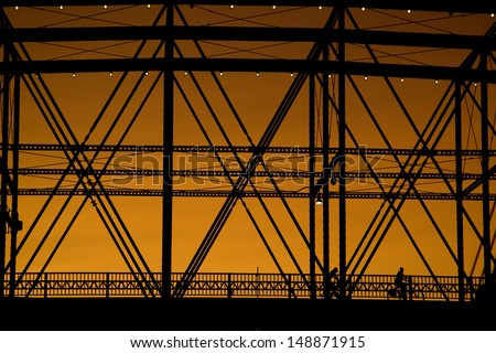 Silhouette of bikers on a steel bridge in Pittsburgh PA at sunset - stock photo