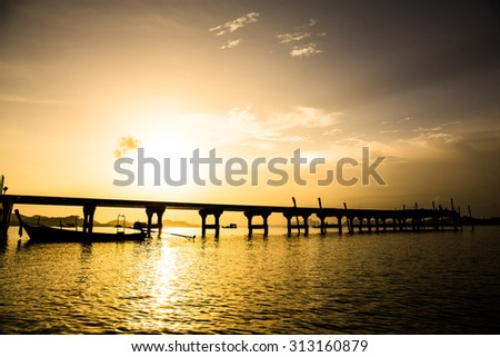 silhouette of boat and bridge at sunlight in sea before sun set