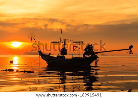 Silhouette of boat in sea at sunset - stock photo