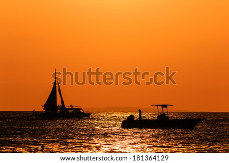 Silhouette of boats against an orange sunset sky on a calm ocean - stock photo