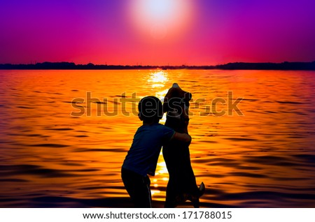 Silhouette of boy and dog hugging at sunset - stock photo