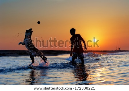 Silhouette of boy and dog playing on the beach at sunrise. - stock photo