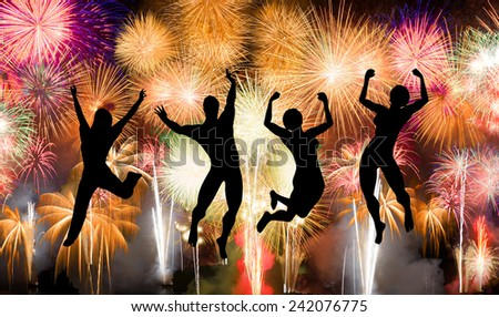 Silhouette of boy and girl jumping happy enjoy brightly colorful fireworks in the night sky - stock photo