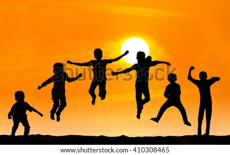 Silhouette of boy and girl jumping over sunset