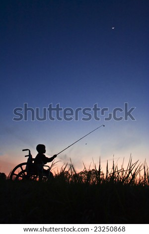 Silhouette of boy in wheel chair fishing at sunset - stock photo
