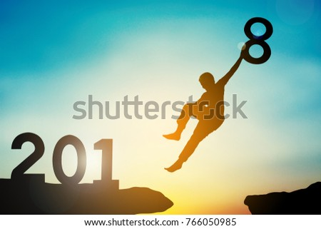 Silhouette of boy jumping with 2018 word at sky sunset, concept Happy New year
