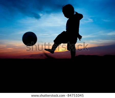 silhouette of boy kick the ball - stock photo
