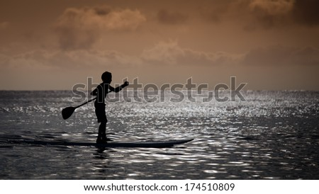 Silhouette of Boy on Paddle Board at Sunset - stock photo