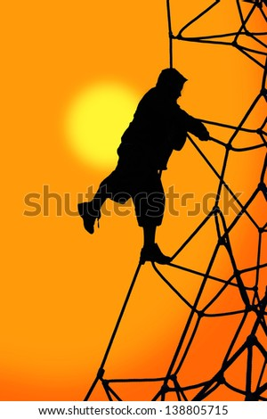 Silhouette of boy on rope climbing frame at sunset