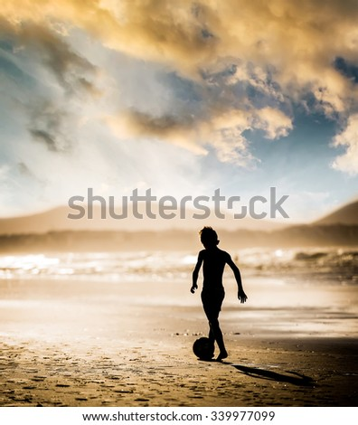 Silhouette of boy on the beach, playing football at sunset - stock photo