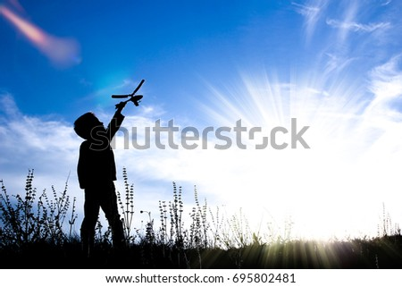 silhouette of boy play with Helicopter on sunset