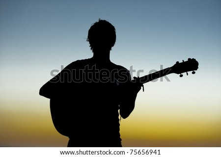 silhouette of boy playing guitar against sunset