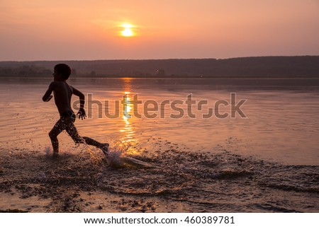 Silhouette of boy running on river's beach against sunset, space for text