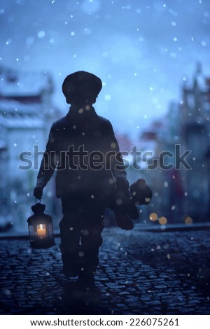 Silhouette of boy, standing on stairs, holding lantern and teddy bear, view of Prague behind him, snowy evening - stock photo