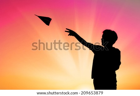 silhouette of boy throwing paper plane - stock photo