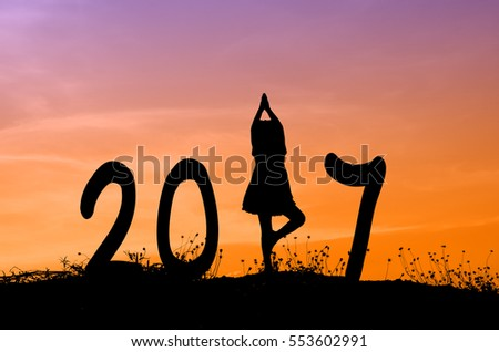 Silhouette of boy yoga girl and 2017 with sun set.