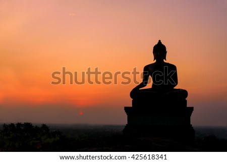 Silhouette of Buddha in a temple at Thailand evening