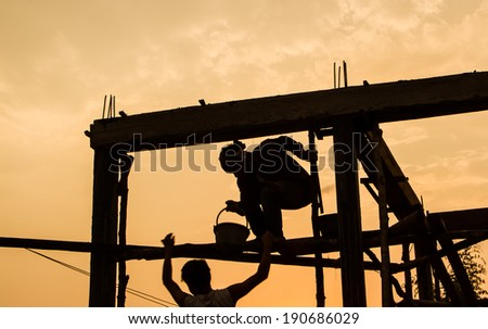 Silhouette of builder working with sunset.